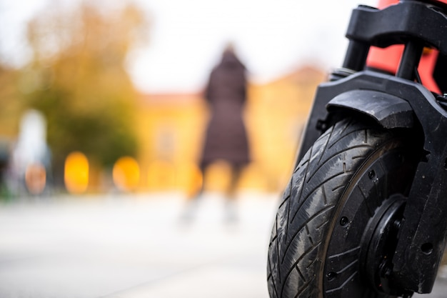 Closeup shot of a wheel of a motorcycle with a person standing in the back