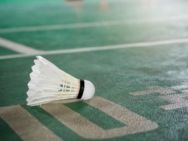 Closeup shot of white badminton shuttlecock on green court.