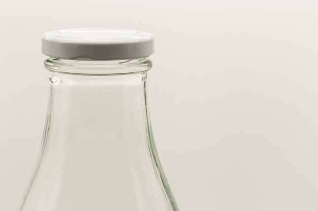 Colpo del primo piano di una bottiglia bianca con un tappo su di esso