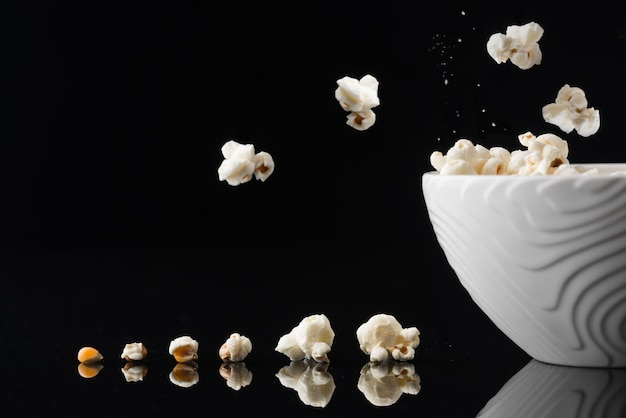 Closeup shot of a white bowl with popping pop-corn out of it on a dark background