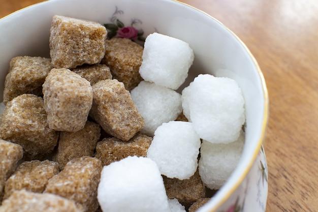 Primo piano di cubetti di zucchero bianco e marrone in una ciotola bianca su un tavolo di legno