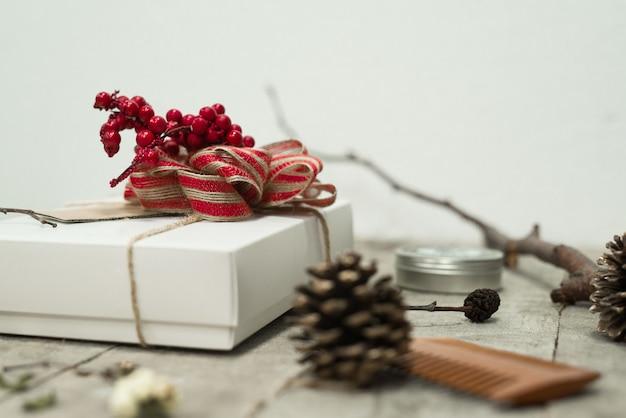 Colpo del primo piano di un contenitore di regalo di natale bianco con un fiocco rosso sopra sul tavolo vicino alle pigne