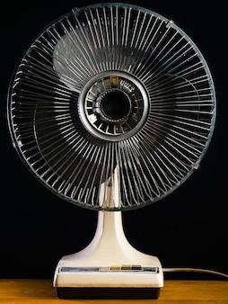 Colpo del primo piano di un ventilatore da tavolo bianco su un tavolo di legno