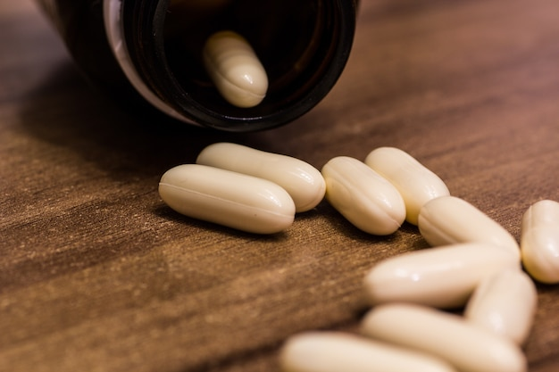 Closeup shot of white medicine capsules on a wooden surface