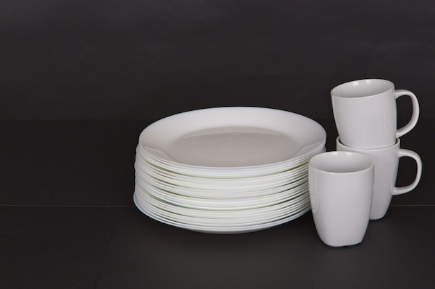Closeup shot of white plates and mugs on a black background