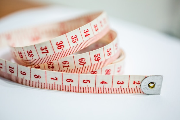 Closeup shot of a white and red tape measure on the table under the lights - designing concept