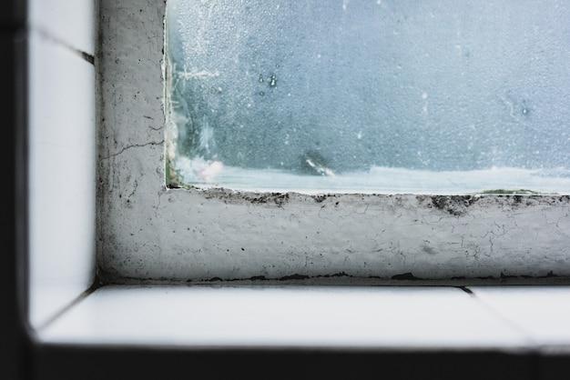 Colpo del primo piano di un davanzale selvaggio con una vecchia finestra e il vetro coperto di glassa