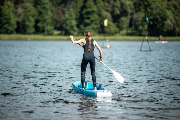 Primo piano di una donna con una tuta sportiva nera che rema su un lago in una competizione di sup