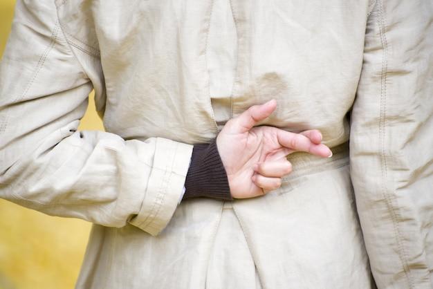 Colpo del primo piano di una donna che incrocia le dita dietro la schiena
