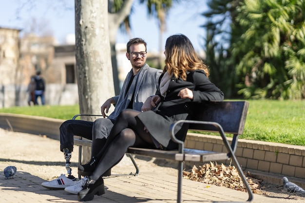 Closeup shot of a woman and a disabled young man with foot prosthesis sitting outdoor