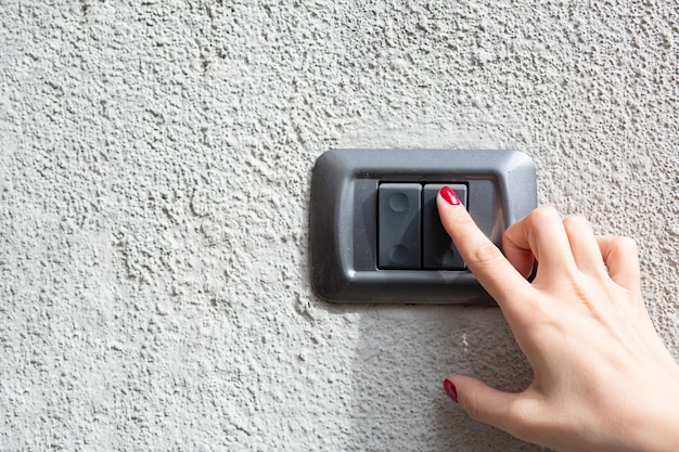 Closeup shot of woman hand pressing the button of a doorbell on concrete wall. empty space