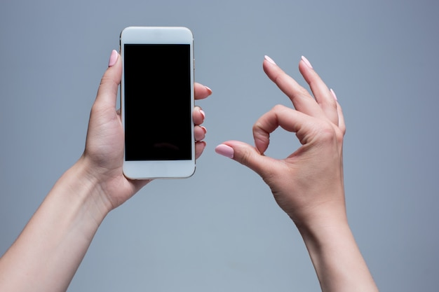 Colpo del primo piano di una donna che digita sul telefono cellulare su sfondo grigio. mani femminili che tengono uno smartphone moderno e che indicano con figer. schermo vuoto per inserirlo nella tua pagina web o messaggio.