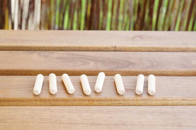 Colpo del primo piano dei perni di costruzione in legno su un tavolo di legno