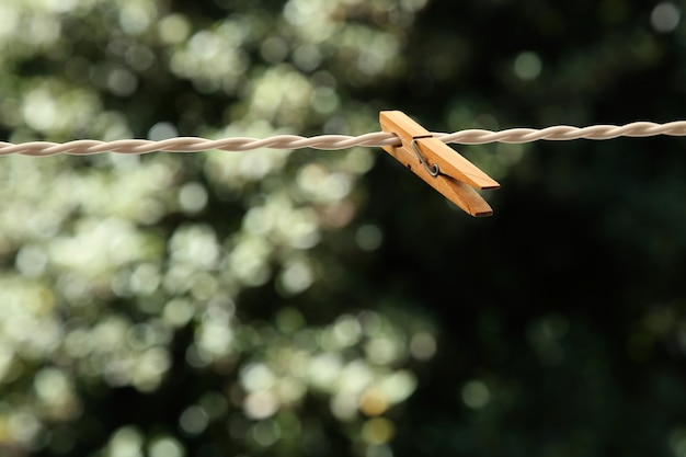 A closeup shot of a wooden clothespin on a wire with a blurred natural background