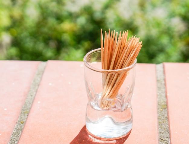Colpo del primo piano di stuzzicadenti di legno in un piccolo bicchiere