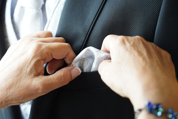 Closeup shot of the wrinkled hands of a female fixing the handkerchief of a groom