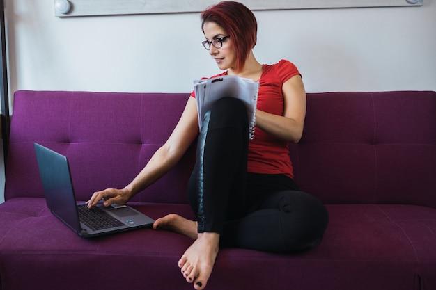 Primo piano di una giovane bella donna che scrive e si siede sul divano davanti al laptop