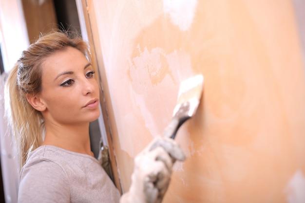 Colpo del primo piano di una giovane donna bionda che dipinge il muro sotto le luci