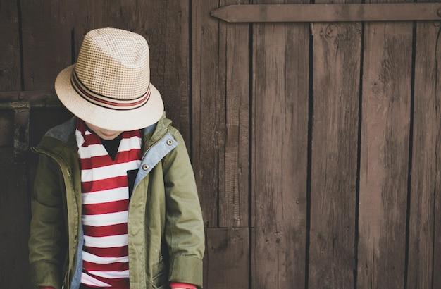 Colpo del primo piano di un giovane ragazzo con un cappotto verde, una camicia a righe e un cappello su uno sfondo di legno