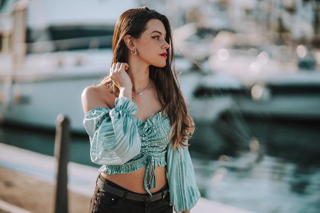 Primo piano di una giovane donna europea con una camicetta turchese