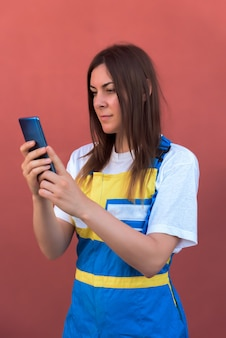 Closeup shot of a young female with her smartphone posing at camera