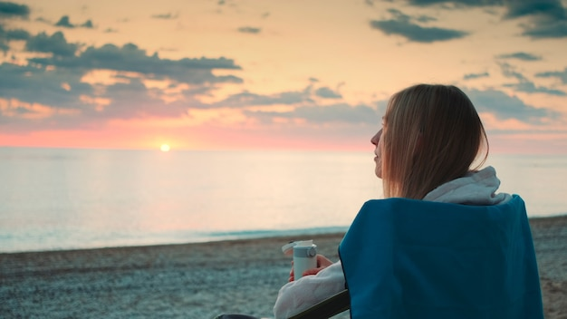 Closeup shot of young woman drinking from thermos and sitting on camping chairs on the beach