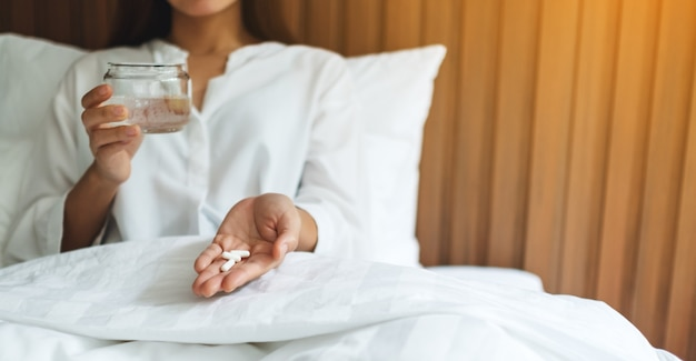 Closeup  of a sick woman holding white pills and a glass of water while lying down on a bed