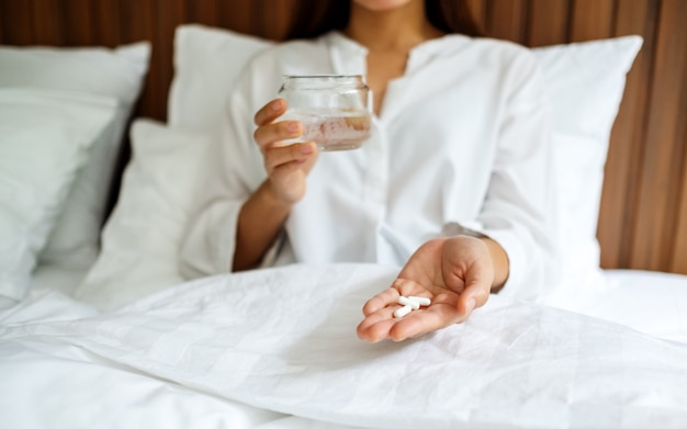 Closeup  of a sick woman holding white pills and a glass of water while sitting on a bed