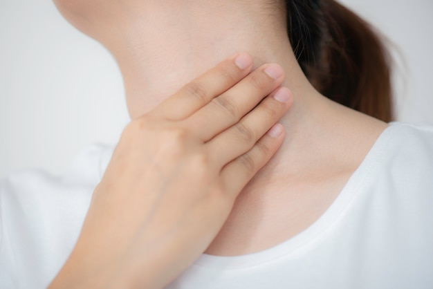 Closeup of sick young woman hand touching her neck with sore throat.