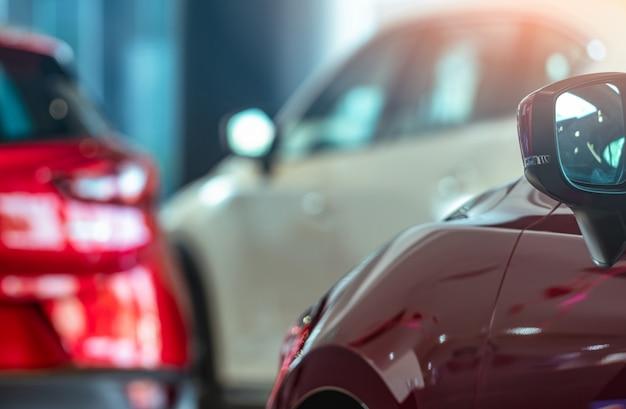ぼやけているsuvの赤い車のクローズアップサイドミラーがモダンなショールームに駐車。カーディーラー。オートリースのコンセプト。ショールームの在庫。