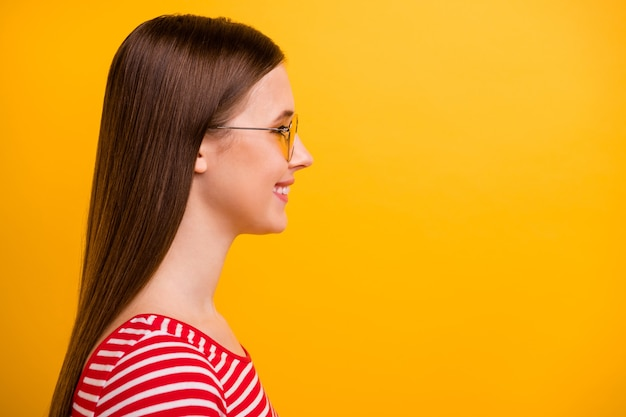 Closeup side photo of pretty lovely young girl beaming smiling look empty space promising promotion sales shop opening wear sun specs striped white red shirt vibrant yellow color background