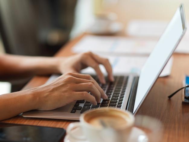 Крупным планом вид сбоку женских пальцев, печатающих на клавиатуре ноутбука в конференц-зале