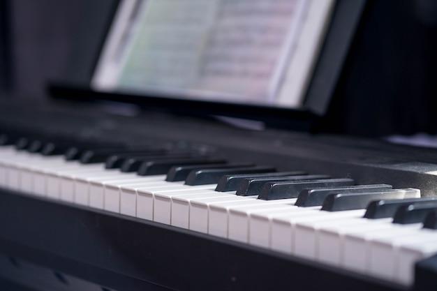 低光のピアノキーボードのクローズアップの側面図