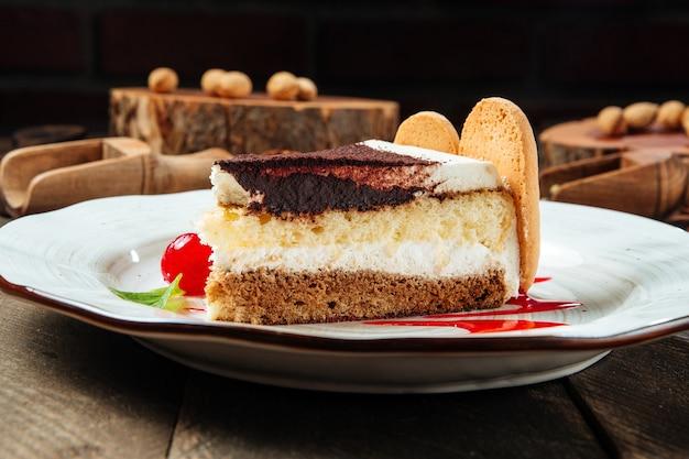 木製のテーブルの上のベリーソースとティラミスケーキのクローズアップ側面図