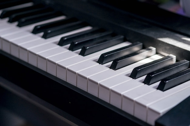 Closeup side view of piano keyboard with low light