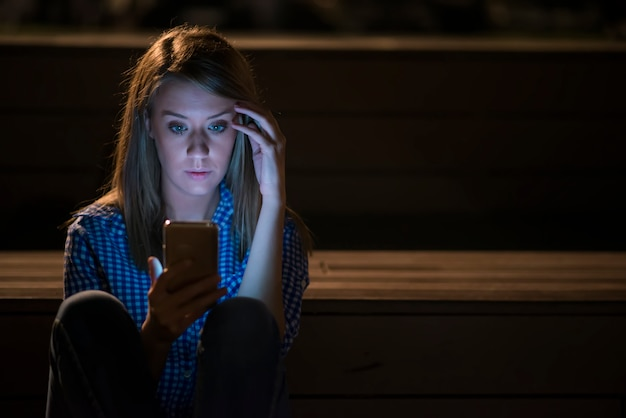 Closeup side view portrait of young sad thoughtful woman leaning against street lamp at night on bokeh copy space background, upset young woman with mobile phone reads the message.