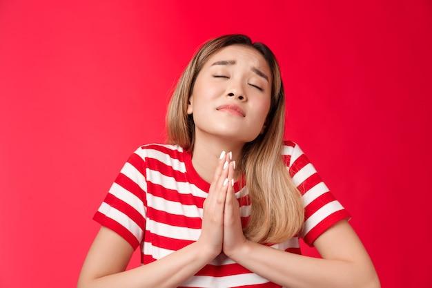 Крупным планом глупая обнадеживающая азиатская девушка со светлой прической просит бога помочь держаться за руки, молиться, моля поднять ...