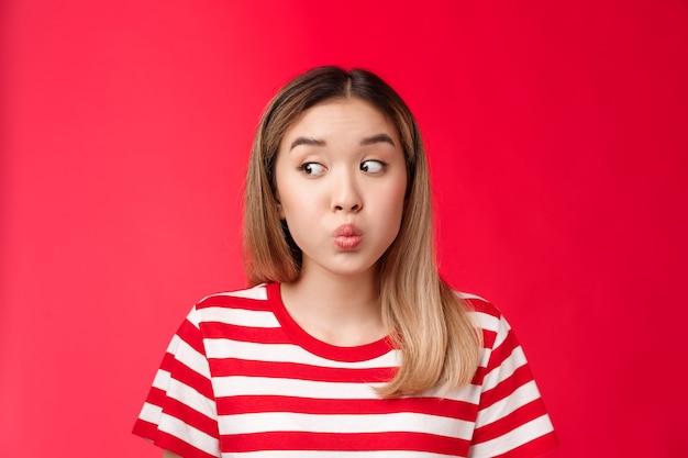 근접 촬영 어리석은 부드러운 젊은 현대 아시아 여자 금발 머리는 숨을 접는 입술과 삐걱 거리는 모습을 잡고...