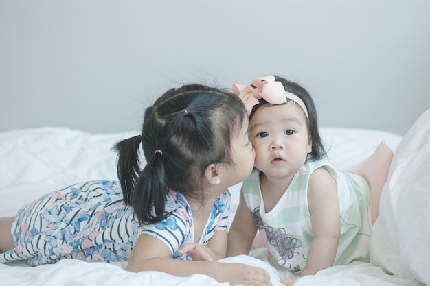 Closeup sister kiss a little girl on bed