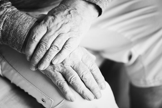 Primo piano di seduta mani anziane