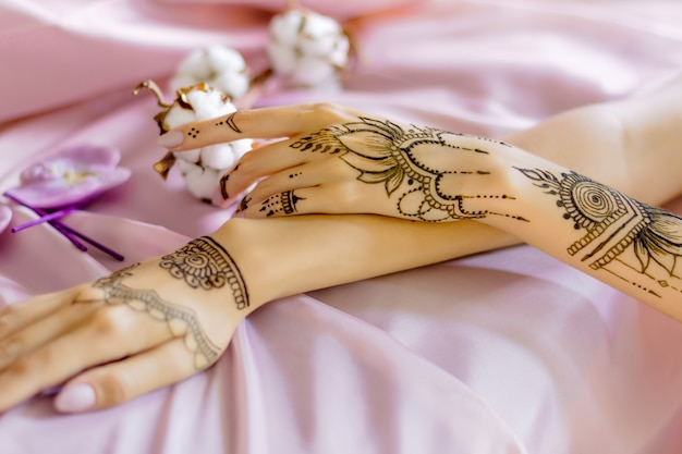 Closeup slender female wrists painted with traditional indian oriental mehndi ornaments. womens hands decorated with henna tattoo. light pink fabric with folds, cotton flowers on background.