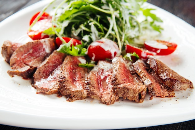 Closeup on sliced roast beef with greens and tomatoes on a white plate