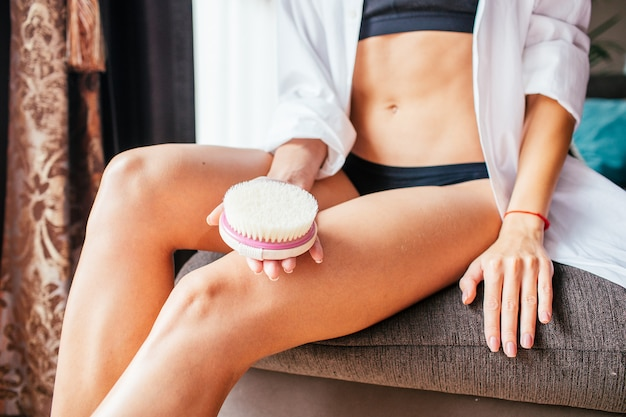 Closeup slim woman in black underwear with natural wooden soft massage brush. cosmetology, grooming, anti-cellulite, exfoliantion and skincare concept.
