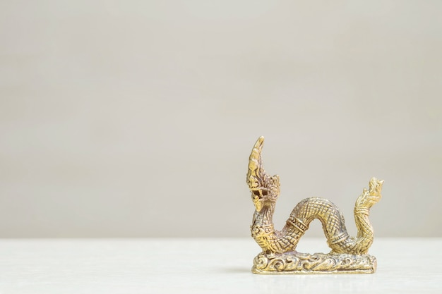 Closeup small brass king naga statue on wood desk