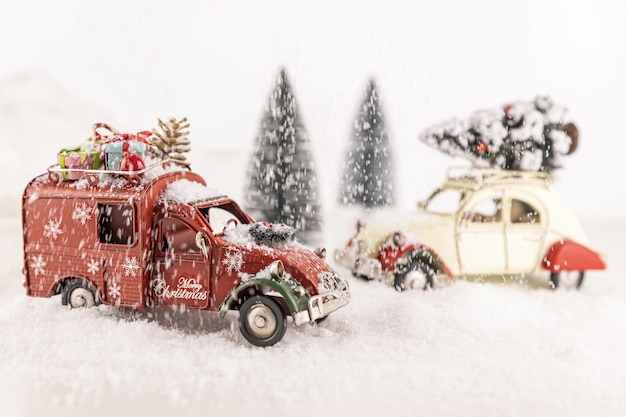 Closeup of small car toys on artificial snow with small christmas trees on the background
