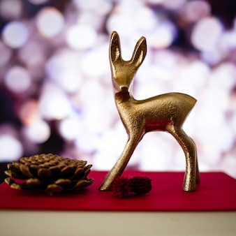 Closeup of a small deer figure and a pine cone on a book with a blurry background and bokeh lights