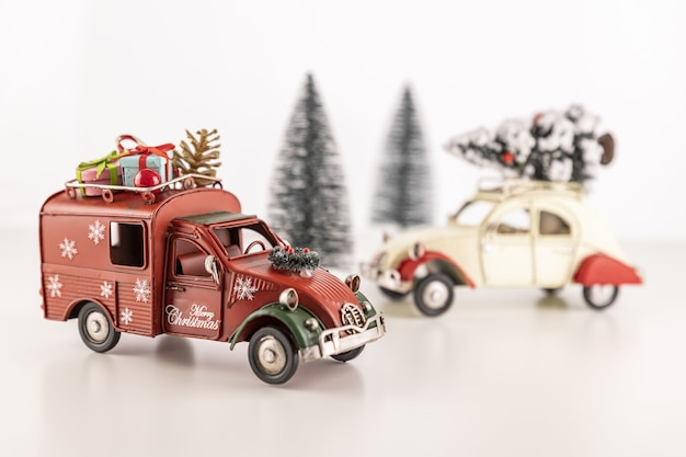 Closeup of small toy cars on the table with small christmas trees in the background