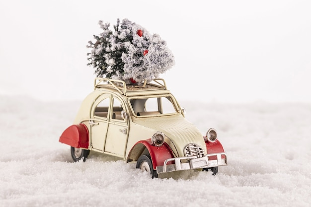 Closeup of a small vintage toy car with a christmas tree on its roof on snow