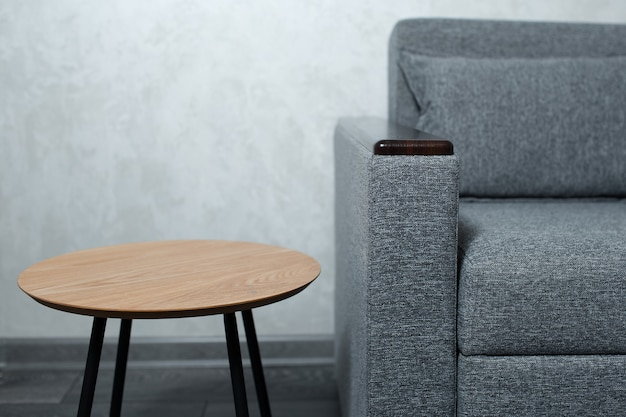 Closeup of small wooden round table near grey sofa on background of textured wall.