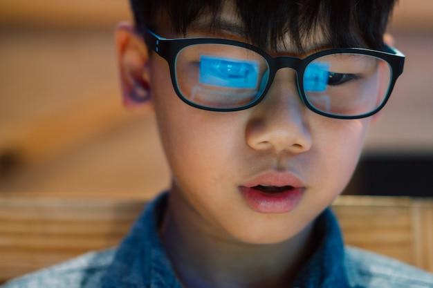 근접 촬영, 스마트 봐 아시아 초반 / 청년 소년 농도와 gamification에 흥분, 컴퓨터 노트북 화면에서 푸른 빛 차단 안경을 쳐다 본다. 컴퓨터 화면의 반사.